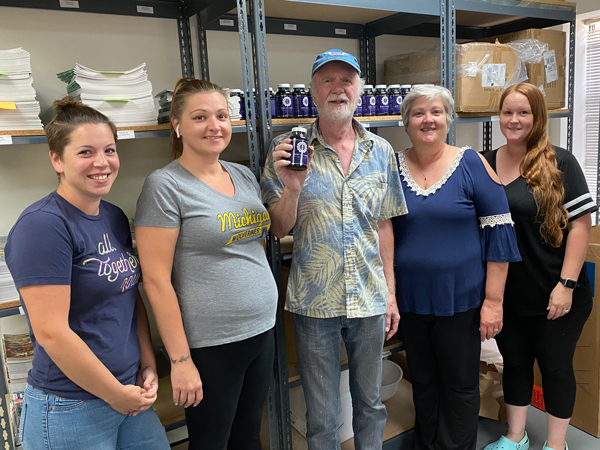 William and office staff with first shipment of vitamins